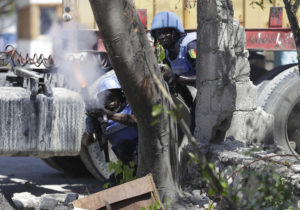 A U.N. peacekeeper from Senegal fires tear gas in front of a truck carrying food aid, as troops clash with rock-throwing neighborhood residents outside a U.N. base in Les Cayes, Haiti, Saturday, Oct. 15, 2016. Residents said clashes with the peacekeepers began when trucks carrying food aid arrived at the base. (AP Photo/Rebecca Blackwell)